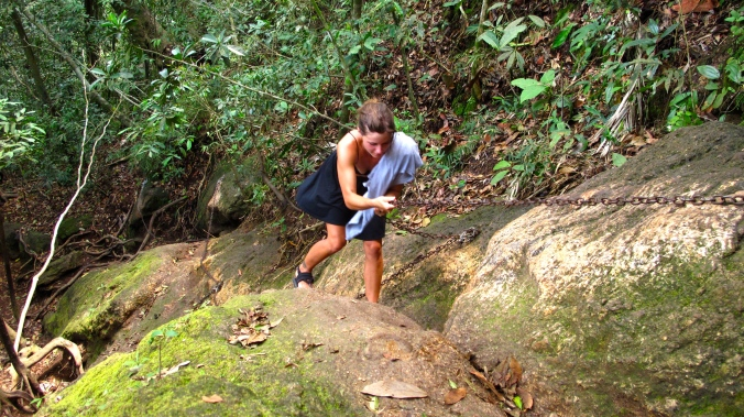 Using the chain to climb up the rocks... in a skirt and flip flops. Great choice Liz